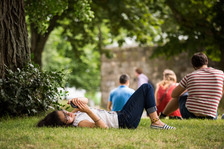 Student lying on the grass under a tree